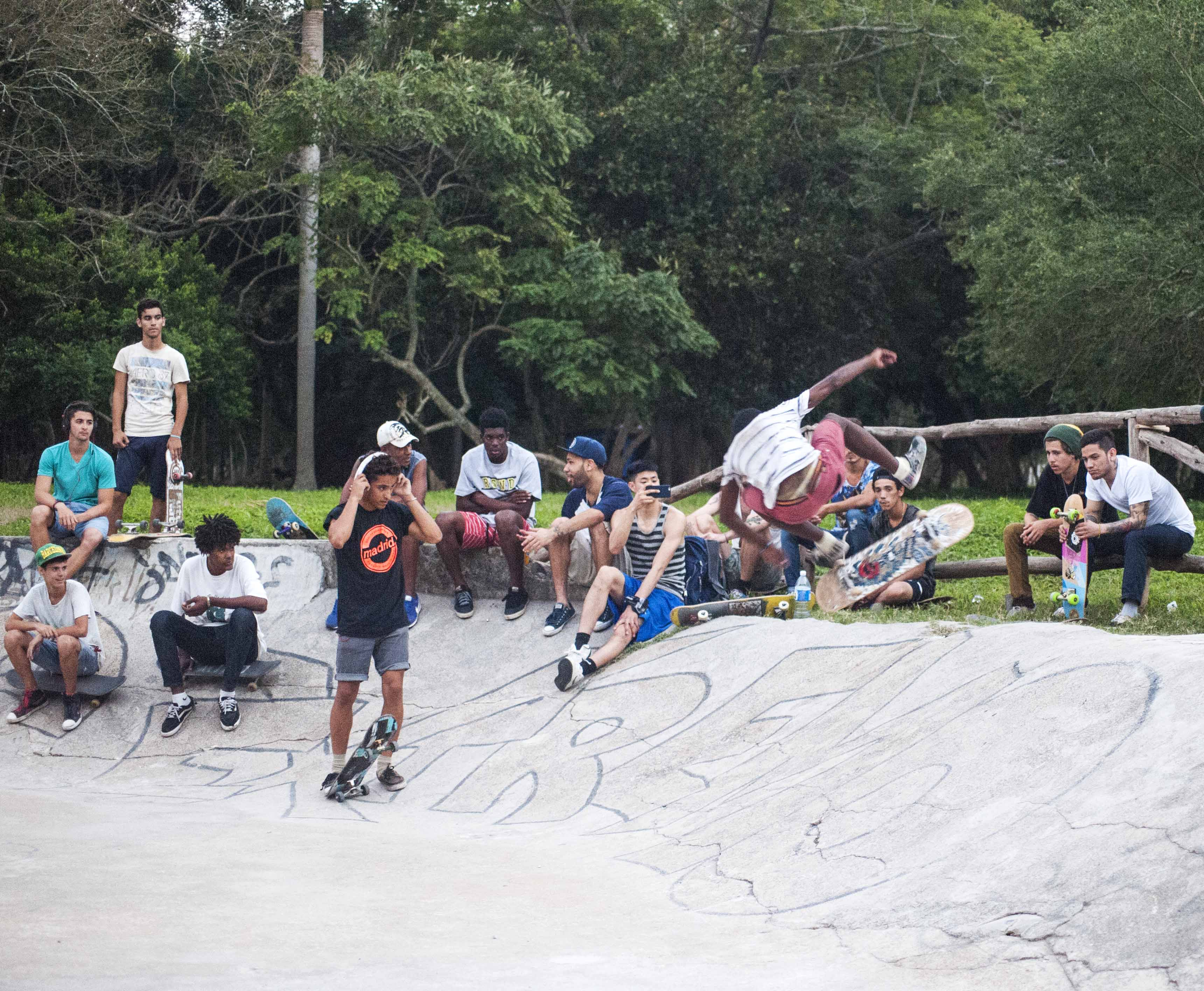Skaters and friends look on as Camilo practices heel flips to fakie. Photo: Neftalie Williams